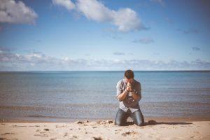 ビーチで祈る男