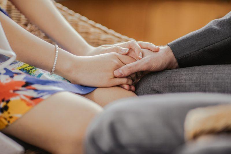 椅子に腰掛けて手を繋ぐカップル